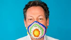 Künstlerin Mansha Friedrich zeigt eine zur Corona-Pandemie gehäkelte Atemschutzmaske