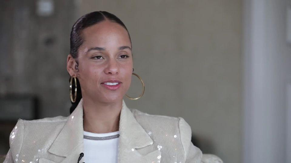 Alicia Keys sitzt in einem Sessel und spricht. Sie trägt einen hellgrauen Blazer und große, goldene Creole-Ohrringe
