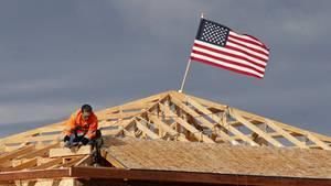 Die US-Flagge weht auf einem Hausdach, das sich in Bau befindet