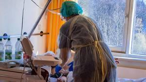 Ein Arzt spricht auf einerIsolierstation für Coronavirus-Behandlungen mit einem Patienten