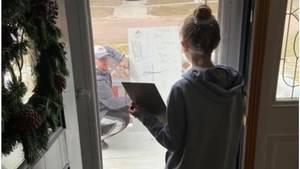 Lehrer erklärt Schülerin vom Hof aus Mathe, er hat eine Tafel dabei