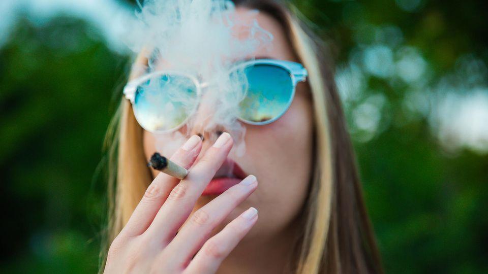 Eine junge Frau raucht einen Joint