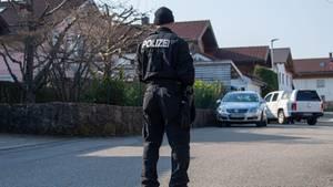 Ein Polizist steht auf der Straße vor dem Haus in Vogtareuth, in dem drei Tote Menschen aufgefunden worden waren