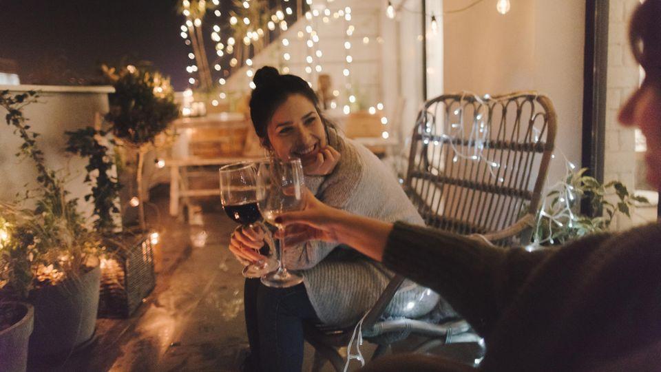 Zwei Frauen sitzen auf dem Balkon und stoßen mit Wein an