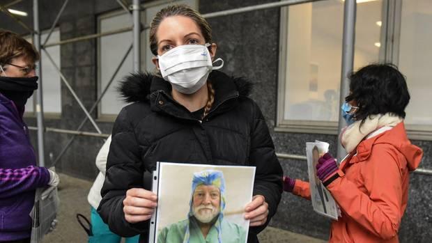 Eine Angestellte des Mount-Sinai-Krankenhauses in New York hält dasBild eines am Virus verstorbenen Kollegen hoch