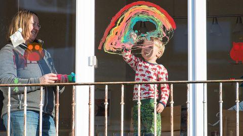 Ein Junge malt einen Regenbogen an die Fensterscheibe