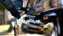Ein Mann steht neben einem Auto und hält einen Schraubenzieher in der Hand. Er trägt schwarze Handschuhe
