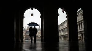 Ein Paar schützt sich mit einem Regenschirmen vor dem Regen, während sie über den Markusplatz spazieren