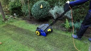 Rasen vertikutieren: Mann bearbeitet seinen Rasen mit einem Elektro-Vertikutierer