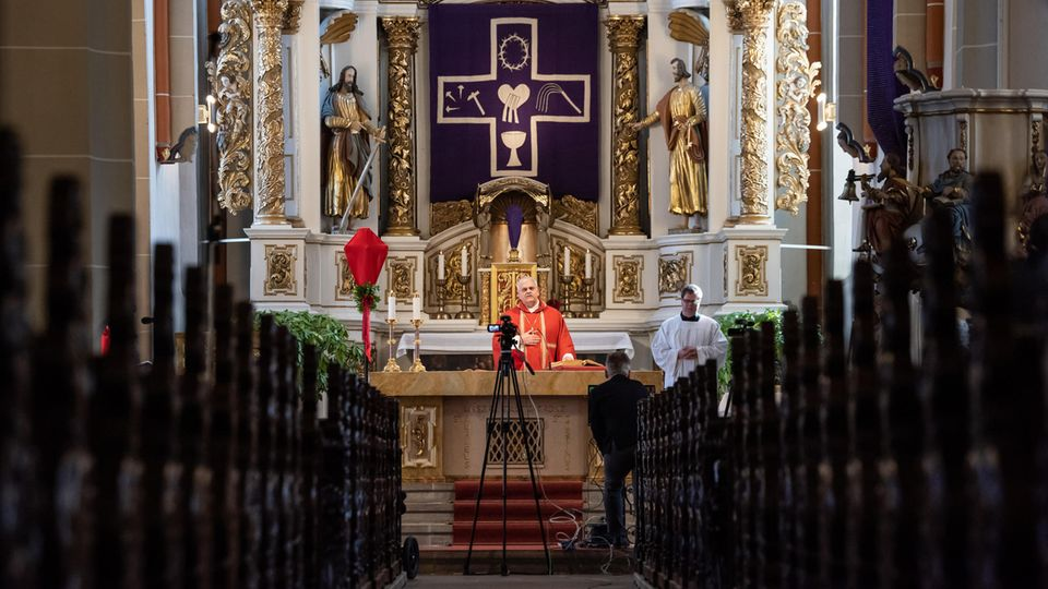 DerErfurter Weihbischof Reinhard Haukehält einen Gottesdienst in einer leeren Kirche vor einer Kamera ab
