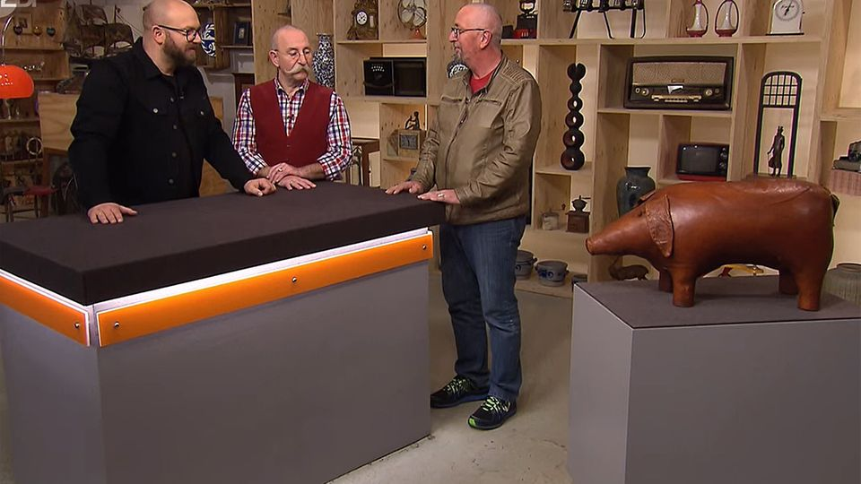 """""""Bares für Rares""""-Experte Sven Deutschmanek und Moderator Horst Lichter bestaunen das Leder-Schwein vonKlaus Groenewald."""