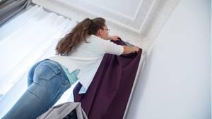 Gardinen waschen und pflegen: Frau steht auf einer Leiter und hängt einen Vorhang auf