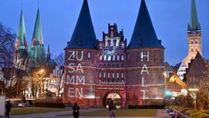 Das Holstentor in Lübeck - beleuchtet mit der Botschaft dieser Tage: Zusammenhalt