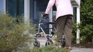 Alte Frau vor Seniorenheim als Symbolfoto für Nachrichten aus Deutschland