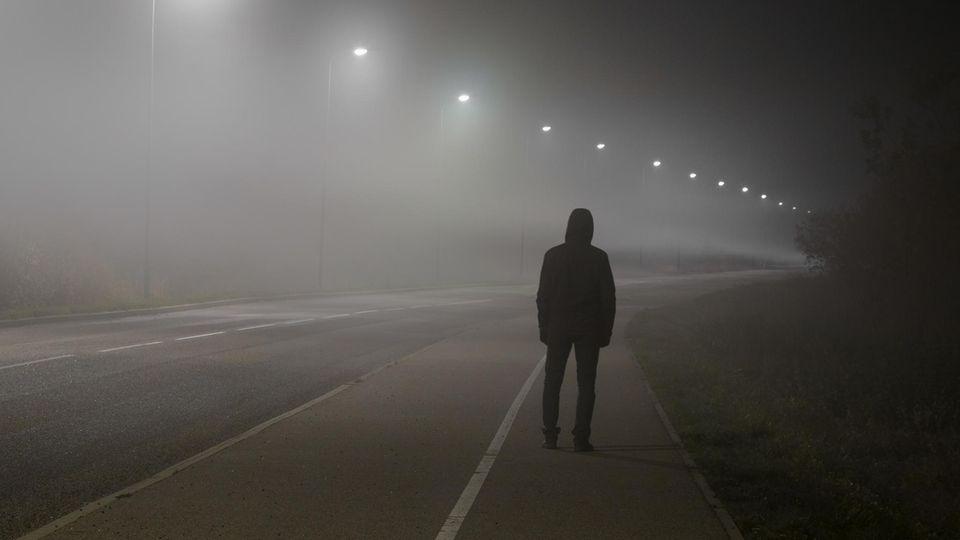 Ein in schwarz gekleideter junger Mann steht von hinten allein an einer Straße