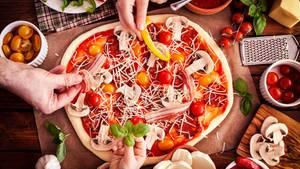 Eine Pizza wird mit Gemüse belegt