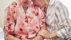 Alte Frauen umarmen sich und lachen