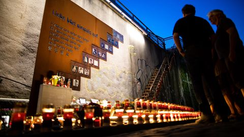 Menschen stehen an der Unglücksstelle der Loveparade 2010