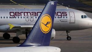 Hinter einem Leitwerk mit Lufthansa-Logo steht ein Flugzeug mit Germanwings-Schriftzug