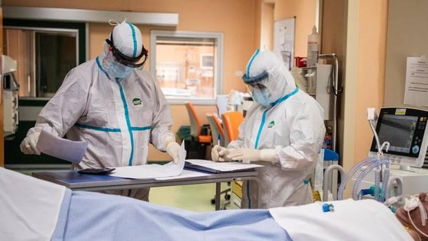 Ein Arzt und eine Krankenschwester in Schutzkleidung arbeiten auf der Intensivstation.