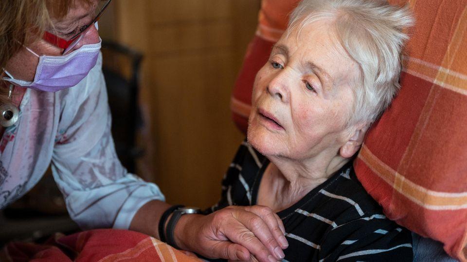 Birgit Rückert, Leiterin eines ambulanten Dienstes, drückt einer Patientin die Hand