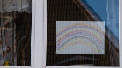 In einer Wohnung hängt eine Regenbogen-Zeichnung im Fenster