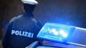 Ein Polizist und ein Polizeifahrzeug