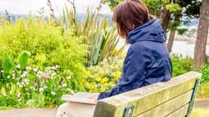 Eine Frau liest ein Buch auf einer Parkbank
