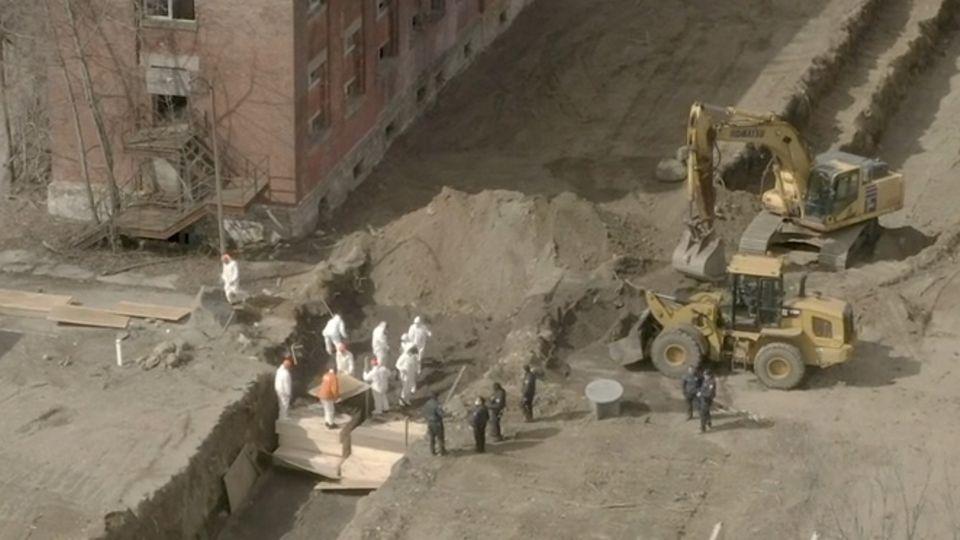 Aufnahmen aus New York: Gefängnisinsassen in Schutzkleidung begraben mehrere Särge in einem Massengrab.