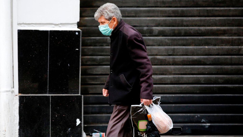 Ein Mann mit Mundschutz geht an einem geschlossenen Geschäft in Algier vorbei