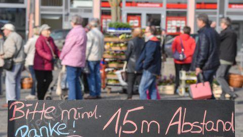 """Ein Schild mit der Aufschrift """"Bitte mind. 1,5 m Abstand Danke!"""" mahnt die Menschenauf einem Markt in Frankfurt/Oder"""