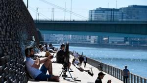 Menschen genießen an Karfreitag das schöne Wetter an der Rheintreppe gegenüber des Kölner Doms. Auch am Wochenende sollen die warmen Temperaturen erhalten bleiben.