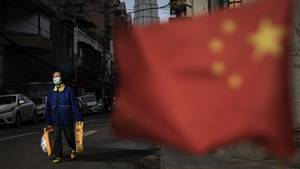 Wuhan, China. Ein Passant mit Einkaufstüten. Im Vordergrund weht die chinesische Flagge.