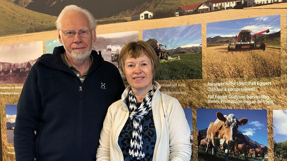 Ólafur Eggertsson und seine Frau Gudny Valberg stehen vor einer Tafel mit Informationen zu ihrer Farm. Eggertsson und Valberg gehörten zu den ersten Isländern, die vom Ausbruch des Eyjafjallajökull vor zehn Jahren betroffen waren.