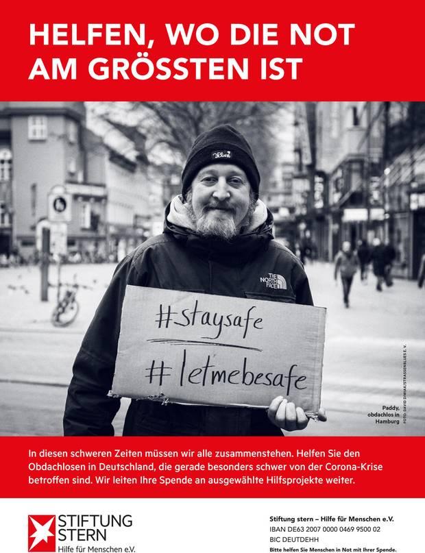 Ein Obdachloser hält eine Pappe mit dem Hashtag staysafe