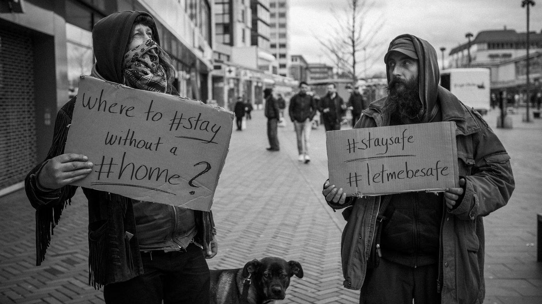 Zwei Obdachlose halten Pappen mit Hashtags