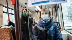 Zwei Frauen tragen in einer Straßenbahnin Jena eine Schutzmaske