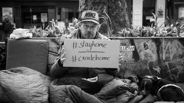 Ein Obdachloser hält ein Plakat
