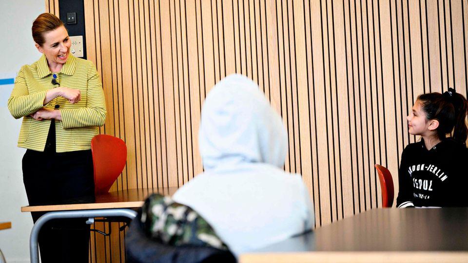 Dänemarks Ministerpräsidentin Mette Frederiksen (l.) spricht mit Schülern in derLykkebo Schule in Kopenhagen