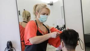 Eine blonde Friseurin in rotem T-Shirt trägt einen Mundschutz, während sie einem Mann die braunen Haare schneidet