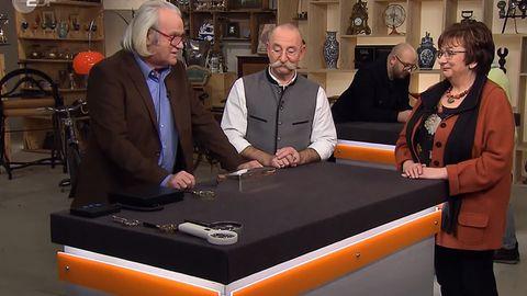 """""""Bares für Rares""""-Experte Albert Maier erklärt Horst Lichter und Verkäuferin Lotti Jungblut die Punzen auf der Silberdose."""