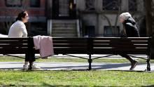 ZweiFrauen sitzen mit Abstand zueinander auf einer Bank und unterhalten sich