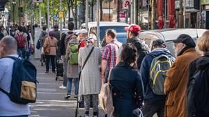 Männer und Frauen unterschiedlichen Alters stehen bei Sonne auf einem Fußweg Schlange