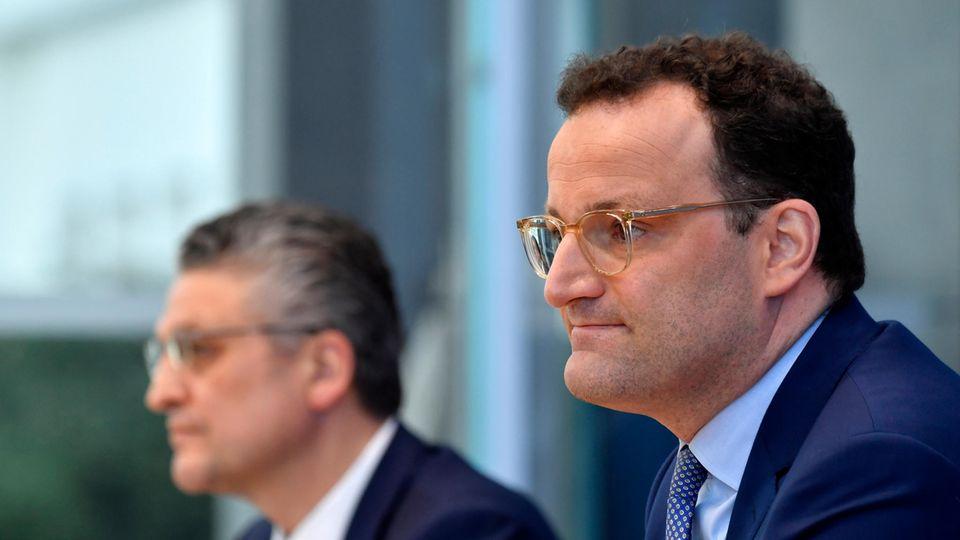 Vor einer blauem Wand sitzen Gesundheitsminister Jens Spahn und RKI-Präsident  Lothar H. Wieler