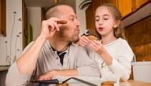 Vater und Tochter essen selbst gebackene Kekse