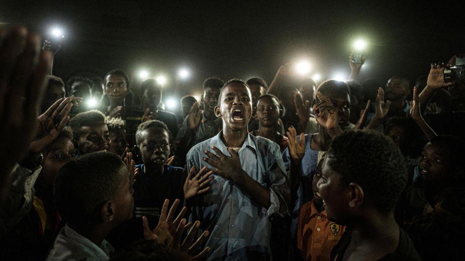 """""""World Press Photo of the Year"""" und Gewinner in der Kategorie """"General News"""":Ein junger Mann rezitiert mitten in einer Gruppe von Demonstranten und im Schein vieler Handy-Lampen Gedichte in Sudans Hauptstadt Khartoum. Der japanische Fotograf Yasuyoshi Chiba ist mit diesem für die französische Agentur AFP aufgenommenen Foto """"Straight Voice"""" Sieger des renommierten Wettbewerbs """"World Press Photo 2020"""" und erhält den mit 10.000 Euro dotierten Preis, wie die Jury des Wettbewerbs """"World Press Photo 2020"""" am 16.04.2020 in Amsterdam mitteilte."""
