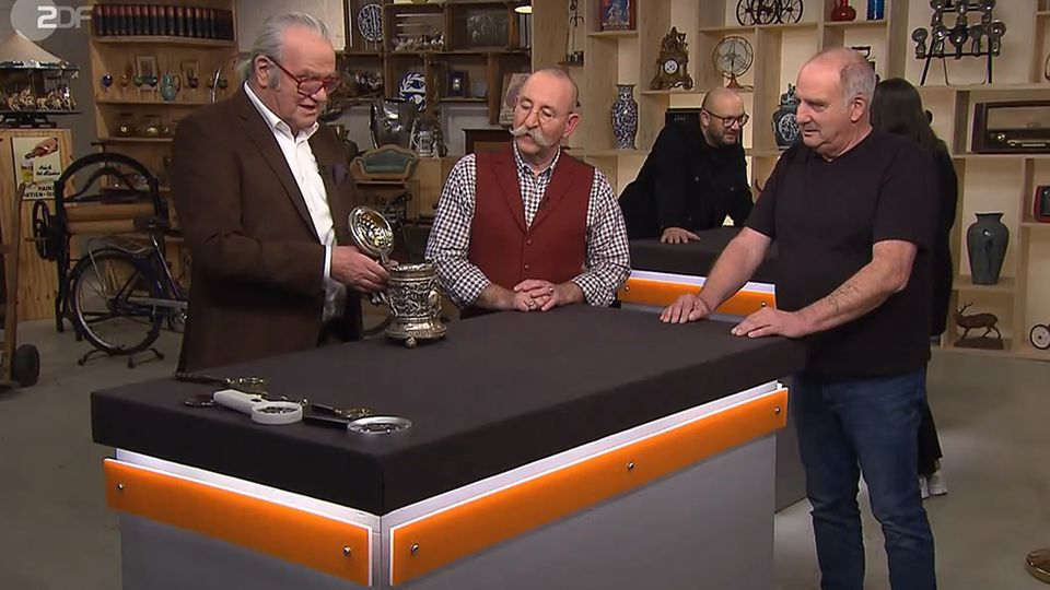 """""""Bares für Rares""""-Experte erklärt die Herkunft des alten Silberkruges. Moderator Horst Lichter und Verkäufer Michael Münz staunen."""