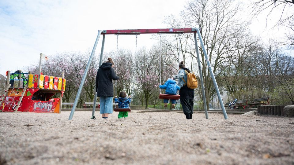 Zwei Mütter mit ihren Kindern auf dem Spielplatz