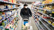 Ein Kunde kauft mit Mundschutz und Handschuhen am frühen Morgen in einem Supermarkt
