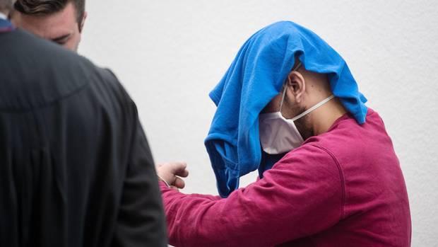 Der Angeklagte betritt in Handschellen, mit einem blauen T-Shirt und Mundschutz den Gerichtssaal